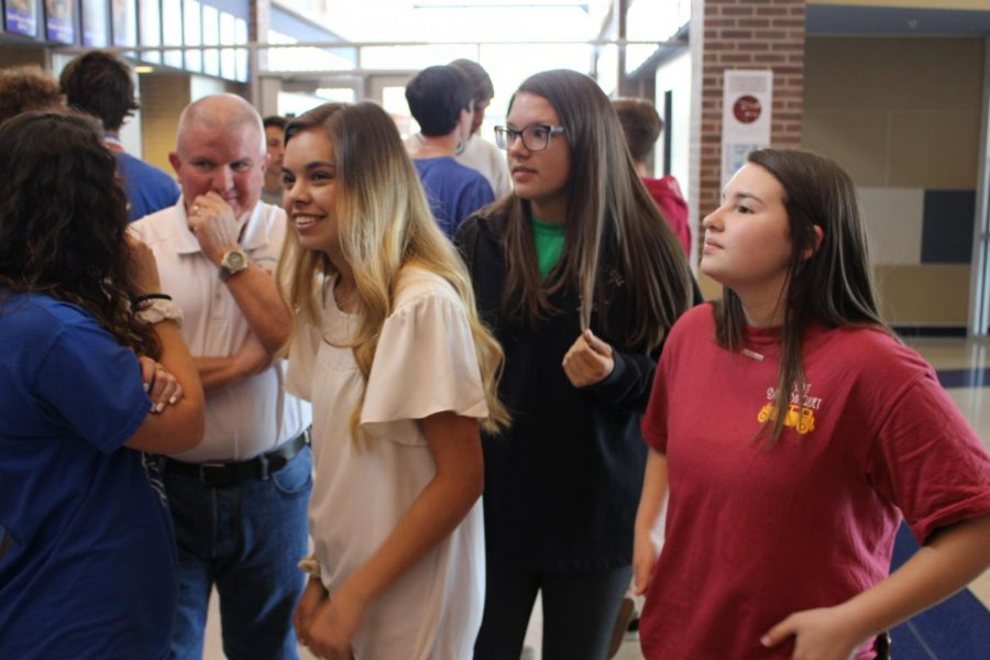 Students and teachers greet each other as school starts back up.