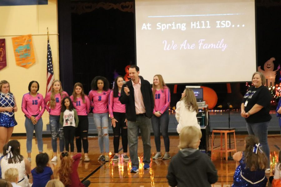 On October 25, Coach Harbison and Varsity Volleyball players present a check to primary student for her family to cover extra expenses as they battle breast cancer.