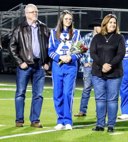 Senior Blue Brigade member, Hope Haney and  her parents are getting ready to walk down the Panther Stadium field at Senior Night.