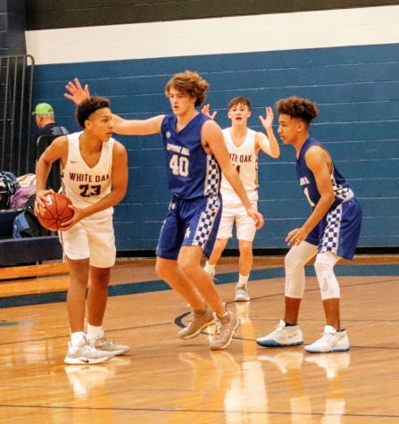 Grayson Crews defends the basket during the 8 AM battle against White Oak.