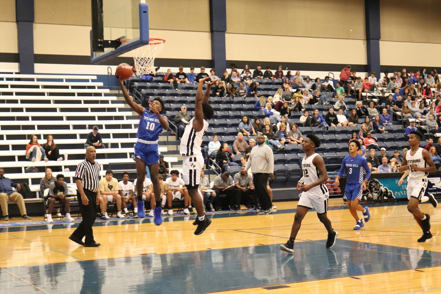 Junior+Curtis+Crowe+goes+up+for+layup+past+defender+in+the+Spring+Hill+High+School+basketball+gym.+