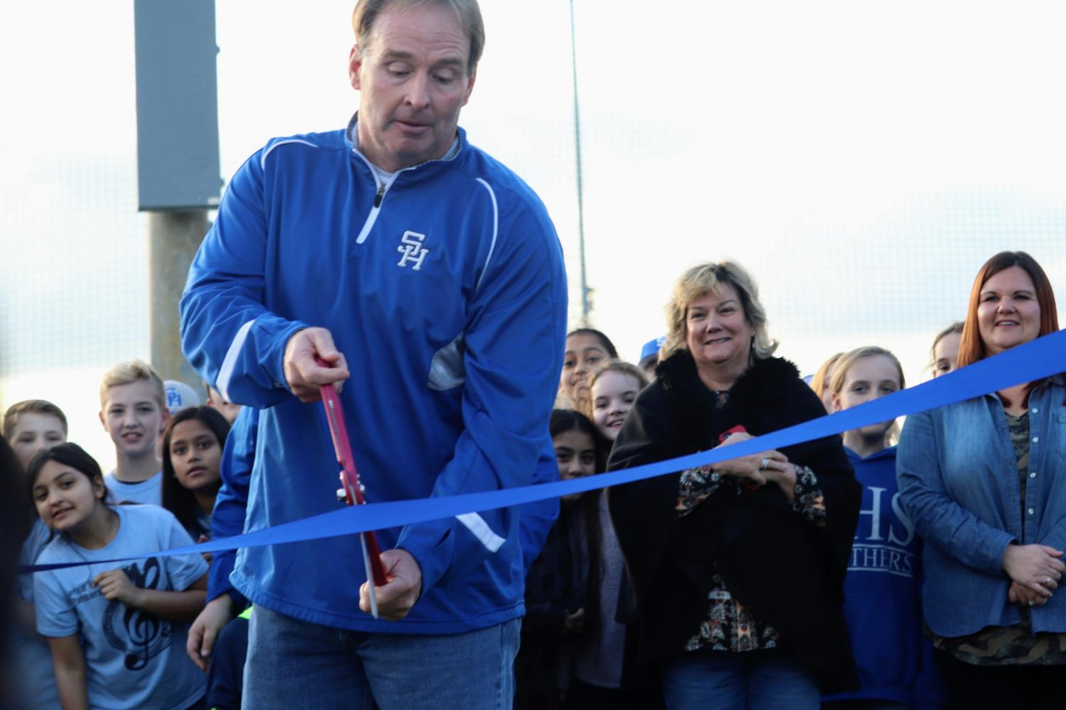 Mark White, SHISD Board President, cuts the ribbon on the new fields.