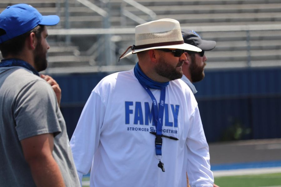 Coach Weston Griffis observes his team at the first day of school football practice.