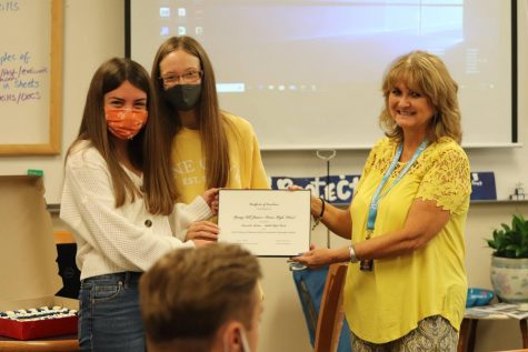Julya Socoteanu and Bailey Ratcliff receive the certificate of award from Neisha Simpson.