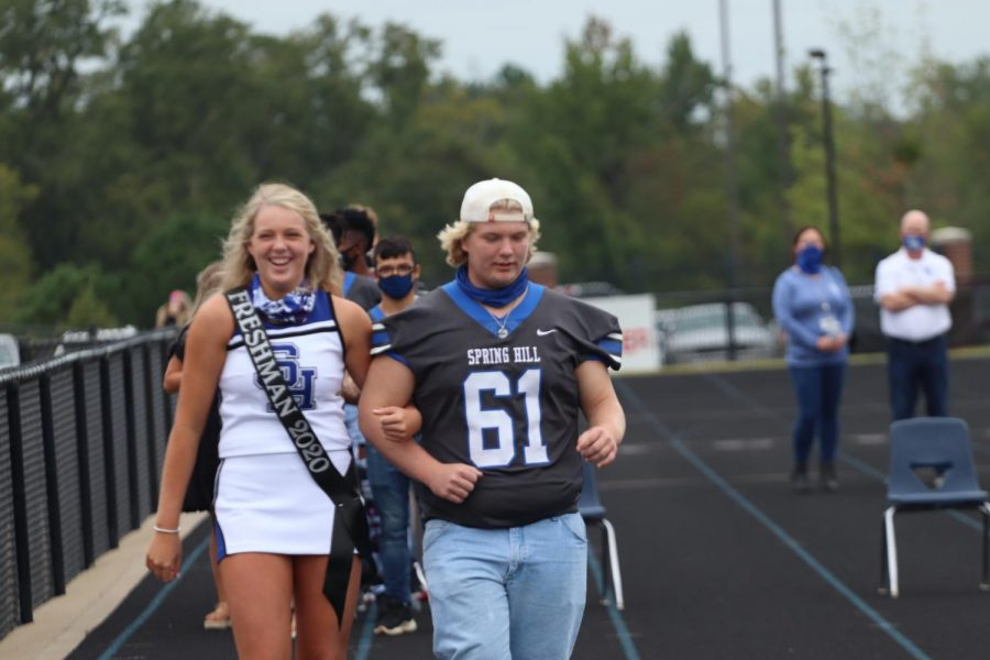 Freshman Carolann Bowles, escorted by her brother Colby walks onto  the field during the homecoming pep rally.
