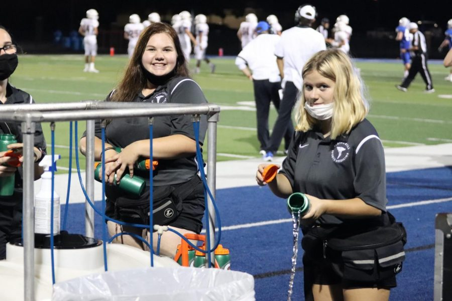 Morgan Foster and Neveah Noorfleet fill water bottles during the Gladewater game in September.
