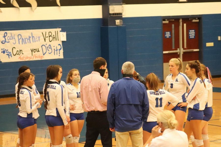 Spring Hill Varsity Volleyball girls huddle around coach Harbison during a timeout in their game against Lindale.