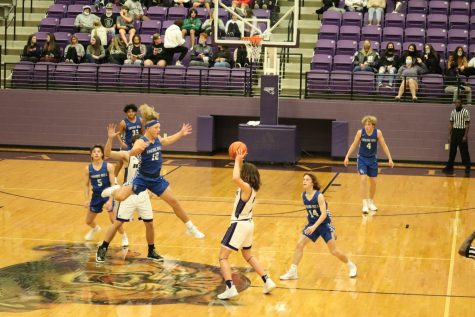 Sophomore Jax Stoval leaps in the air to block the Hallsville Wildcats from passing the ball on the afternoon of December 15, 2020