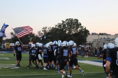 The Panthers rally around the American flag as they run out of the tunnel for their homecoming game against White Oak